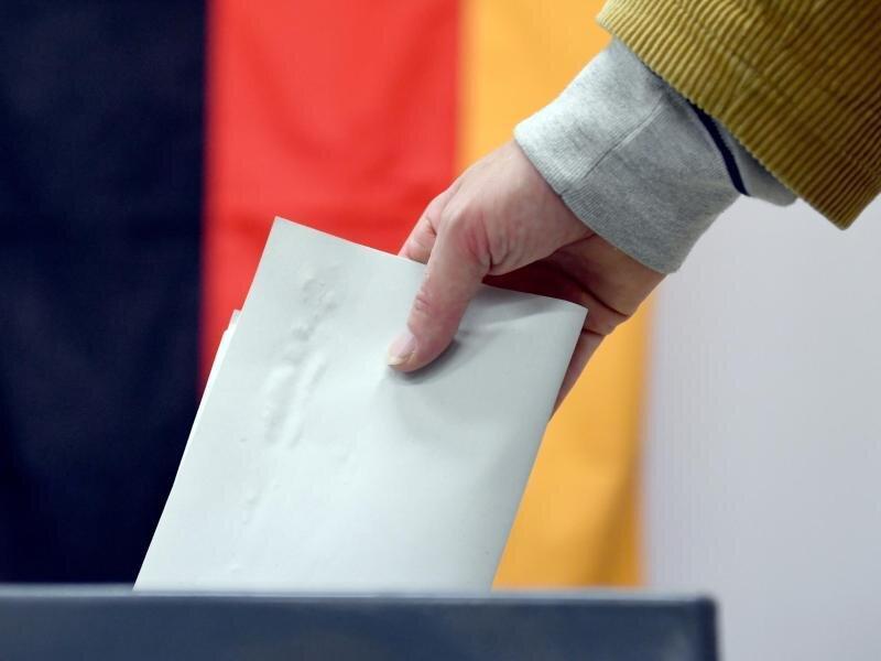 Ein Wähler wirft in einem Wahllokal seinen Stimmzettel in eine Wahlurne.