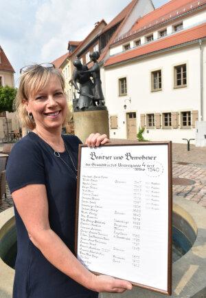 Diana Mader-Schumann, hier mit einer Liste der Inhaber und Bewohner des Hauses Untergasse 4, freut sich mit ihrem Mann Janek über den Sanierungspreis.