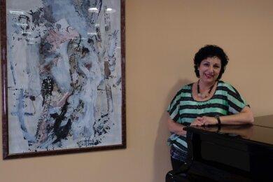Sarah Stamboltsyan, die künstlerische Leiterin der Calliope-Reihe, neben einem der Bilder der Malerin und Grafikerin Marietta Jeschke, die den Saal im Veranstaltungsforum seit ein paar Tagen schmücken.