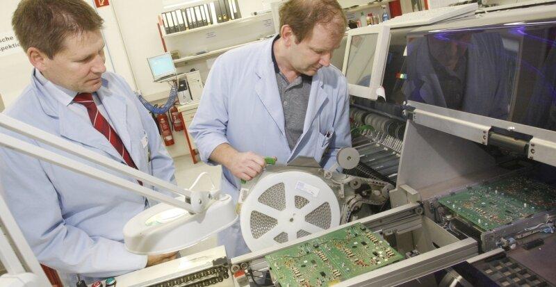 """<p class=""""artikelinhalt"""">Kathrein-Geschäftsführer Andreas Zwißler (links) und Einrichter Volker Ranft kontrollieren einen Automaten, der elektronische Leiterplatten für Kabelnetze bestückt. Bei diesen Bauelementen unter anderem für die Antennen- und Satellitentechnik werden keine Drahtanschlüsse hergestellt, sondern die Anschlüsse direkt gelötet.</p>"""