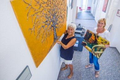 Die Hobbymalerinnen Gabi Sonntag (links) und Ines Burkhardt bauen eine Ausstellung mit ihren Werken im Rathaus Neukirchen auf.