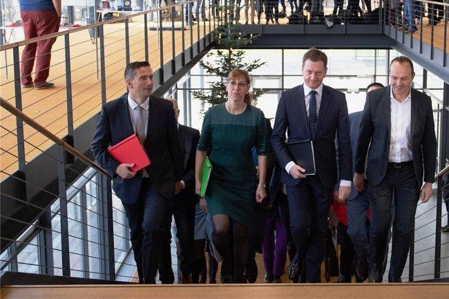Schwarz-grün-rote Einheit: Ministerpräsident Michael Kretschmer (M.), SPD-Chef Martin Dulig (l.) sowie das Grünen-Duo Katja Meier und Wolfram Günther auf dem Weg zur Pressekonferenz, bei der sie den Koalitionsvertrag vorstellen. Im Schlepptau haben sie viele der übrigen Verhandler.