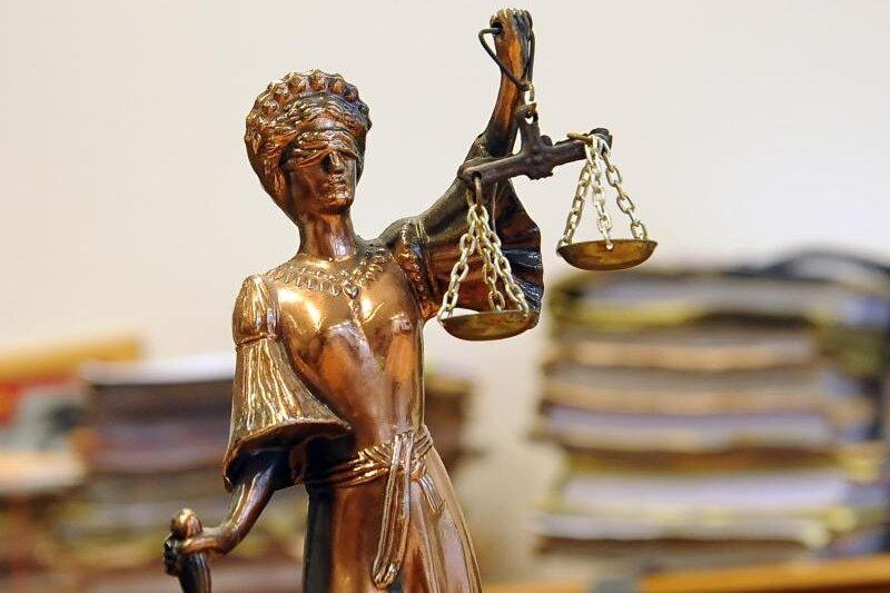 Eine goldfarbene Justitia-Figur steht vor Aktenbergen, die sich auf einem Tisch stapeln.