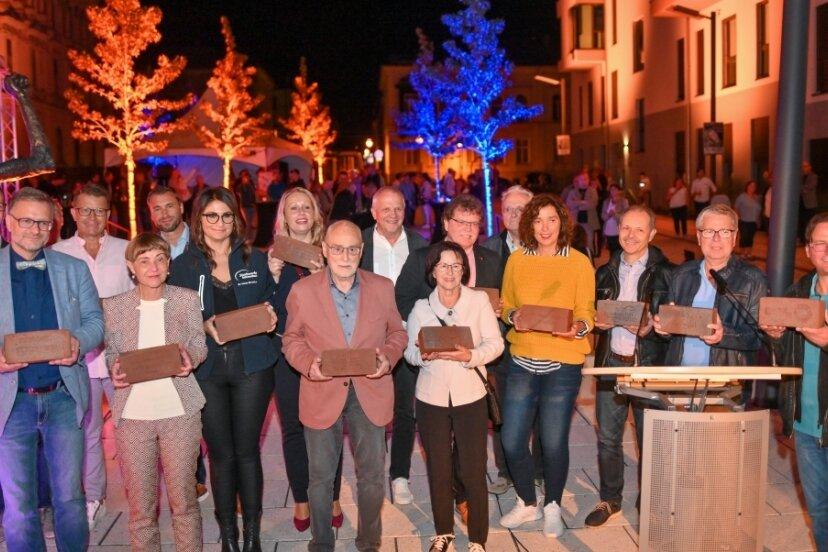 """27 Spender trugen 500 Euro und mehr zum """"Jahrhundertschritt""""-Ankauf bei. Viele von ihnen waren beim Festakt anwesend und fanden sich hier zum Gruppenfoto auf dem illuminierten Solbrigplatz ein."""