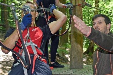 Der Riesaer Udo Stöhr zählt zu den ersten Gästen, die dem Kletterpark Kriebstein einen Besuch abstatten. Parkleiter Marcel Schneider erklärt die Technik.