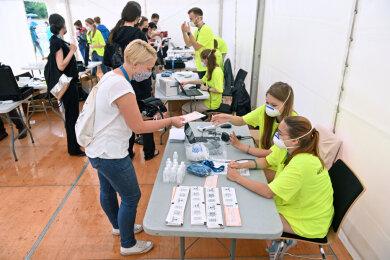 Eine Probandin (vorne, links) steht vor Beginn eines Großversuchs der Universitätsmedizin Halle/Saale am Check-In.