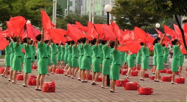 Vor der Arbeit werden - wie hier auf dem Bahnhofsvorplatz von Pjöngjang - am frühen Morgen rote Fahnen geschwenkt. Dazu gibt es aus Lautsprechern Motivationsmusik.