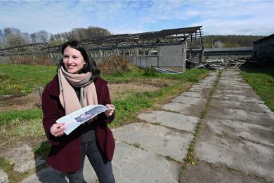 Projektverantwortliche Lara Würfel von der Firma Deto Solarstrom steht auf der Fläche im Unterdorf von Taura, wo eine Fotovoltaikanlage aufgebaut werden soll. Auf dem Gelände gibt es leerstehende Industrie- und Gewerbeflächen.