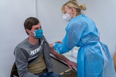Mario Schlegel, Notfallsanitäter aus Markneukirchen, erhält von Dr. Jacqueline Lenk seine Impfung.