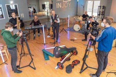 Kameramann Matthias Ditscherlein (vorn, rechts) aus Rodewisch und Sarah Klare (vorn, links) filmen das Konzert der Band Sevenheat im Fitnessstudio.