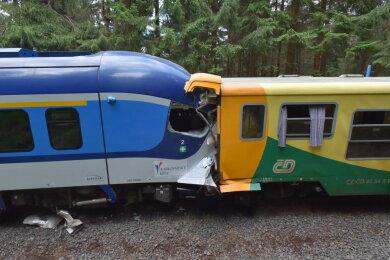 Zwei Züge stehen nach einer Kollision ineinander verkeilt auf einem Gleis.