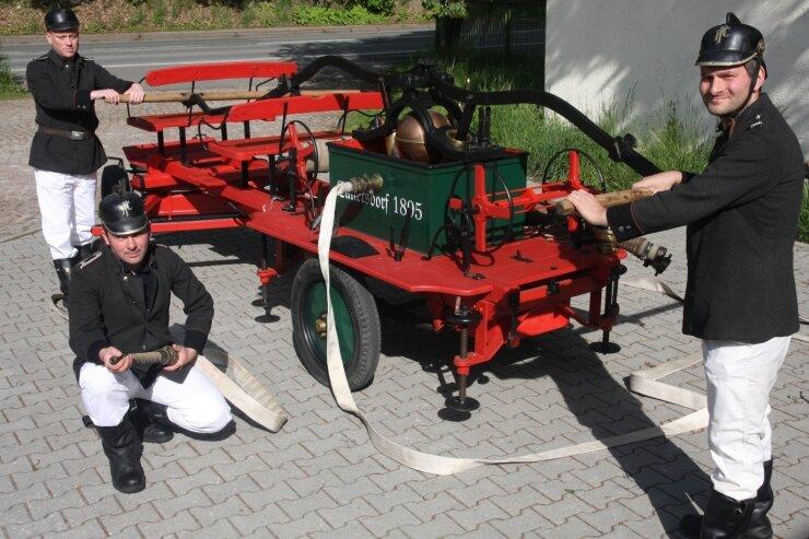 """<p class=""""artikelinhalt"""">Die Freiwillige Feuerwehr Cunersdorf rückt im ersten Teil der Schauübung zum Stadtjubiläum mit der Handkraftspritze aus dem Jahr 1895 an. Veit Müller (hinten) und Alexander Petzold stehen an den Holmen der Pumpe bereit. Thorsten Bauer hält das Strahlrohr für den Löschangriff bereit. </p>"""