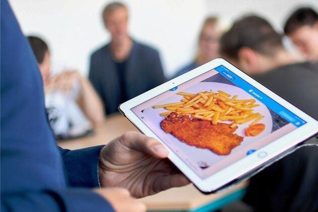 Jasin Peña Cabrera, Englischlehrer am Gymnasium Carolinum, unterrichtet mit Hilfe eines I-Pads, auf dessen Bildschirm ein paniertes Schnitzel mit Pommes frites zu sehen ist. Die Schüler werden so angeregt, auf Englisch über ihr Lieblingsessen zu diskutieren.