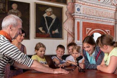 Einige der Porträts der Ahnengalerie im Festsaal von Schloss Rochsburg haben sprechen gelernt. Nils Kochan und Eva Bredow (v. l.) vom Kofferstudio aus Frauenstein haben innerhalb eines Ferienangebotes dieses Audio-Projekt mit Kindern aus dem DRK-Hort Lunzenau umgesetzt.