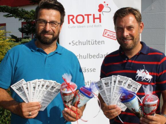 Vertriebsleiter Jens Heinz (l.) und FSV-Vorstandsmitglied Matthias Krauß präsentieren Tauschtickets und Zuckertüten.