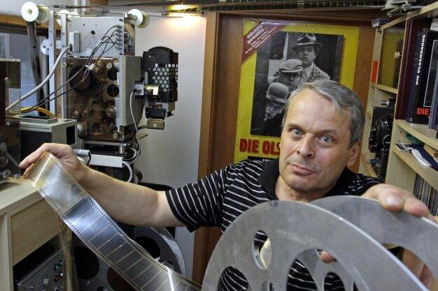 """<p class=""""artikelinhalt"""">Ulrich Göhler präsentiert in seinem Vorführraum, der durch eine Glasscheibe mit dem Wohnzimmer verbunden ist, eine der großen Rollen für die 70-Millimeter-Filme. Links hinten steht sein selbst gebautes Vorführgerät für diese Filme. </p>"""