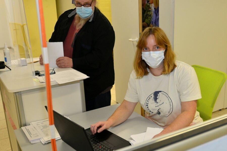 """Im Impfzentrum in Mittweida trifft man Reisebegleiterin Regina Gehmlich und Gastwirt Steffen """"Kuno"""" Kunze an einem Arbeitsplatz, hier ist es die Abmeldung nach der Impfung."""