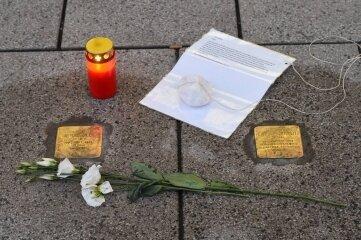 Mitglieder des Agiua-Vereins hatten an Stolpersteinen in der Innenstadt, wie hier an der Brückenstraße, Blumen und Kerzen niedergelegt sowie Biografien der Opfer verteilt. Später ist ein Teil der Platten beschädigt worden.