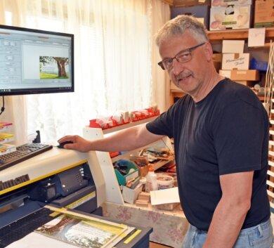Matthias Bilz in seiner Werkstatt in Cämmerswalde. Mit einem speziellen Hochleistungsdrucker kann er Bildmotive auf dünne Holzplatten aufdrucken.