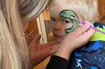 Der zweijährige Wim lässt sich von Franziska Müller einen Saurier ins Gesicht schminken.