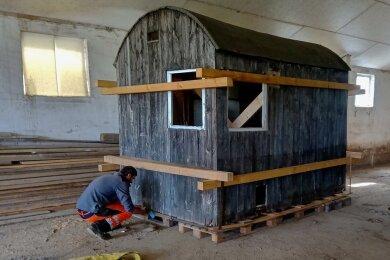 Die Baracke wird mit Kanthölzern für den Transport vorbereitet.