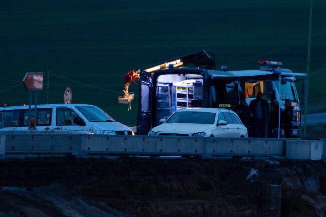 Einsatzkräfte der Polizei untersuchen auf der Bundesstraße 91 ein Taxi. Damit soll der Tatverdächtige versucht haben, zu fliehen.
