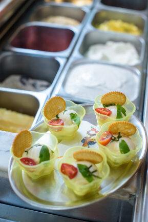 Im Eiscafé Favretti stehen fünf Becher Maggi-Eis, dekoriert mit Tomate, Basilikum, Liebstöckel und einem Salzcracker, zum Verzehr bereit.