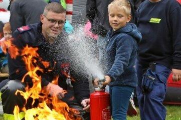 Keine Angst vor dem Feuerlöscher:Erik Werner aus Niederlungwitz (5), Lukas Wolf (9) von der Jugendfeuerwehr und Feuerwehrmann Daniel Beierlein zeigen, wie es geht.