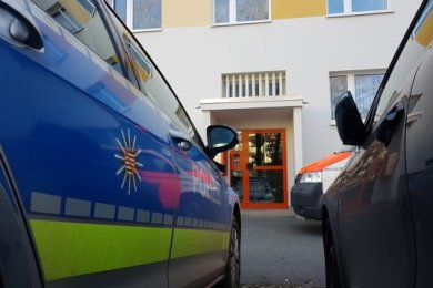 Einsatzkräfte am Eingang zum Wohnhaus an der Straße der Deutschen Einheit