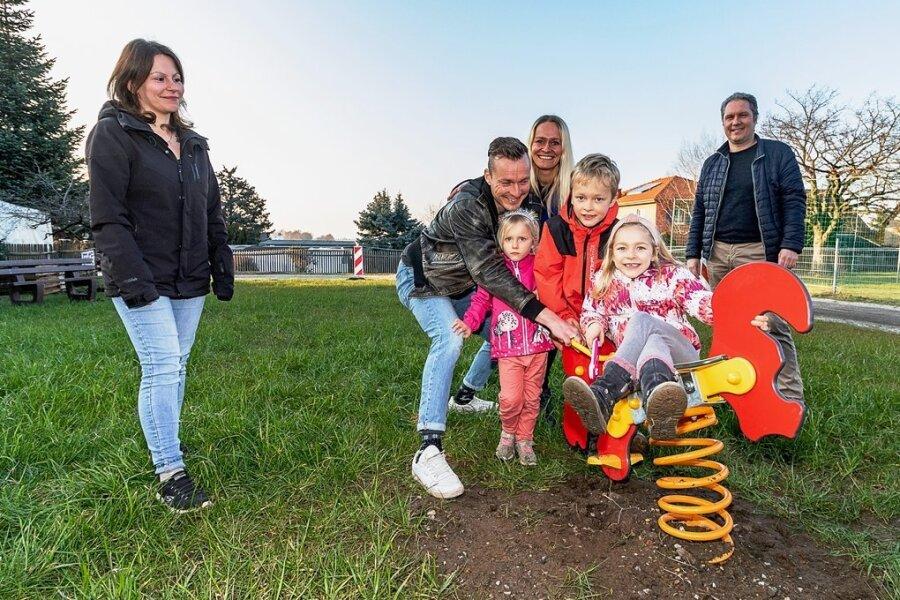 Die Eltern Elisabeth Günther, Matthias und Kristin Huwe sowie Sportvereinschef Mike Kellermann (von links) wünschen sich einen neuen Spielplatz im Burgstädter Ortsteil Herrenhaide. Paloma, Micah und Soléne Huwe (vorn von links) testen schon mal zwei Wipp-Spielgeräte - ein Anfang.