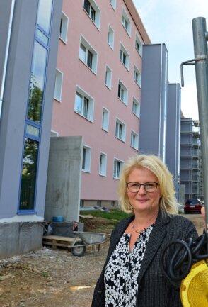 Jutta Bornemann, Geschäftsführende Vorstandsvorsitzende der WG, am Eingang zur Baustelle. Die vorderen drei der insgesamt sieben neuen Aufzugstürme konnten bereits abgerüstet werden.