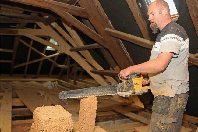 Im Nordflügel des Komplexes: Thomas Stöbe von einer Blankenhainer Firma schneidet auf dem Dachboden Lehmziegel zurecht.