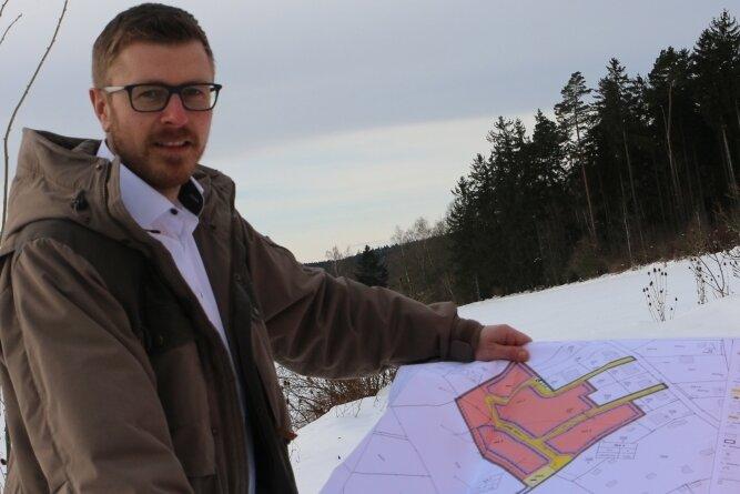 Bürgermeister Michael Frisch zeigt die Bauzeichnung am zukünftigen Standort nahe des Waldes oberhalb von Syrau.