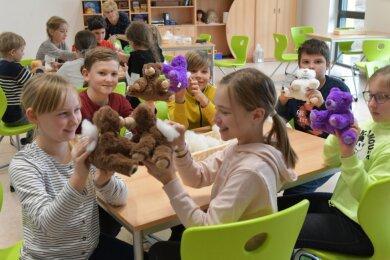 Im Hort der Freiberger Agricola-Grundschule stopften auch die Viertklässler kleine vorgefertigte Teddybären aus. Hanna und Neele (vorn, von links) freuen sich über die kuscheligen Gesellen.
