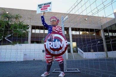 """""""Glaubt nicht den liberalen Medien"""" steht auf dem Schild, das Tara Immen, eine Unterstützerin von US-Präsident Donald Trump, zum Protest vor der Wahlbehörde von Maricopa County (Arizona) hochhält."""