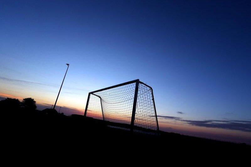 Ein Fußballtor hebt sich auf dem Sportplatz vor dem wolkenlosem Himmel ab.