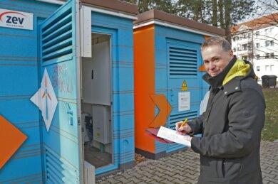 Sven Fischer von der ZEV vor dem Häuschen, das unter anderem einen Energiespeicher beherbergt.