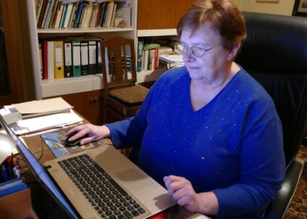Vor einem Regal voller Ordner steht der Computer, an dem OrtschronistinGisela Uhlig ihre zahlreichen Daten auch digital aufbereitet.
