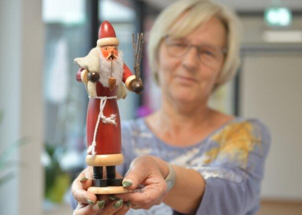Hortleiterin Katrin Hofmann zeigt einen Weihnachtsmann, der aus Bausätzen aus der Werkstatt von Tobias Wolf zusammengesetzt worden ist.