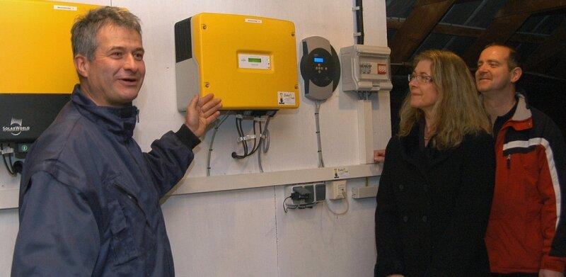 """<p class=""""artikelinhalt"""">Robby Oertel (l.) von der Thumer Firma Elektro Oertel erläutert Sylvi Walther und Uwe Meyer, beide Gesellschafter der Bürgerkraftwerk Mildenau GbR, die Wirkungsweise eines sogenannten Wechselrichters.</p>"""
