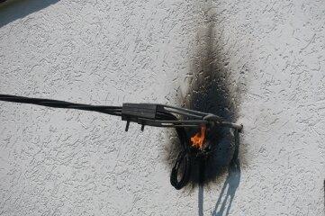 Die brennende Elektroleitung an der Hauswand.