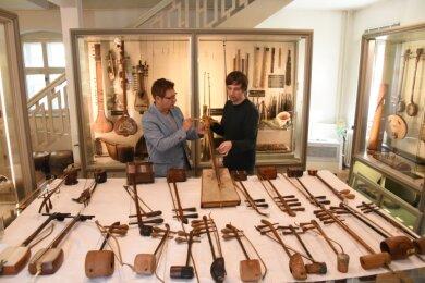 Rolf Killius aus London (links) und Stefan Hindtsche, Leiter des Musikinstrumenten-Museums Markneukirchen, in der Sammlung von Instrumenten aus aller Welt, die im Ostflügel des Museums gezeigt wird und die der Londoner Musikethnologe nun das dritte Jahr in Folge systematisch erforscht. Es geht um fast 300 Instrumente.