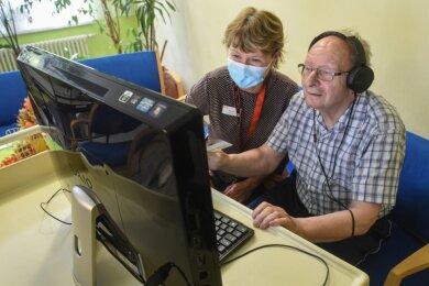 Bewohner Dieter Schneider mit Betreuerin Monika Dabkowski, die ihm beim Bedienen der Technik hilft, vor einem großen Monitor im ASB-Altenpflegeheim an der Rembrandtstraße beim Videotelefonieren mit Angehörigen per Skype.