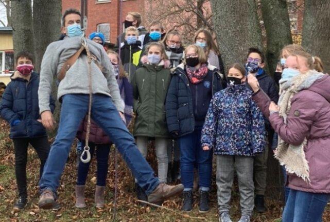 Physikunterricht im Freien: Schulleiter Hendrik Nocht lässt sich von einer Schülerin mittels Flaschenzug heben.