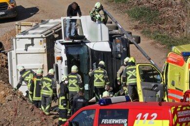 Einsatzkräfte der Feuerwehr befreien den verunglückten Lkw-Fahrer aus seiner misslichen Lage im umgestürzten Kipper.
