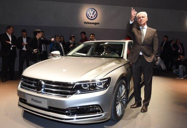 VW-Chef Matthias Müller zeigt sich beim Volkswagen-Konzernabend neben einem VW Phideon.