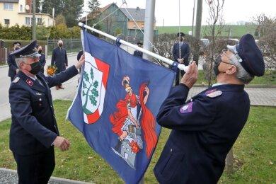 Wolfgang Unger (rechts) und Ronald Landgraf hissen die neue Feuerwehrfahne am Feuerwehrdenkmal neben dem Gerätehaus in Langenberg. Dem folgt eine Schweigeminute für die verstorbenen Kameraden.