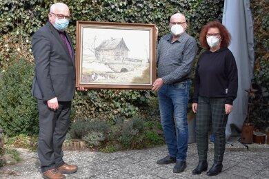 Rathauschef Steffen Ludwig (l.) nimmt das Gemälde freudig von Beate und Otfried Porstmann entgegen.