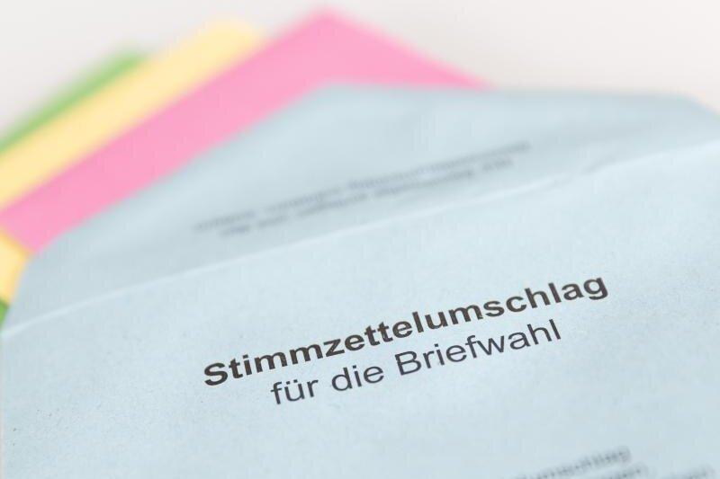 Verschiedene Stimmzettel stecken in einem Stimmzettelumschlag für die Briefwahl.