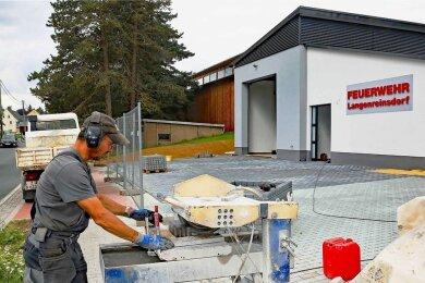 Heiko Hölzel von der Langenreinsdorfer Firma SWT schneidet Pflastersteine für die Außenanlagen des neuen Feuerwehrgerätehauses in dem Crimmitschauer Ortsteil zurecht.